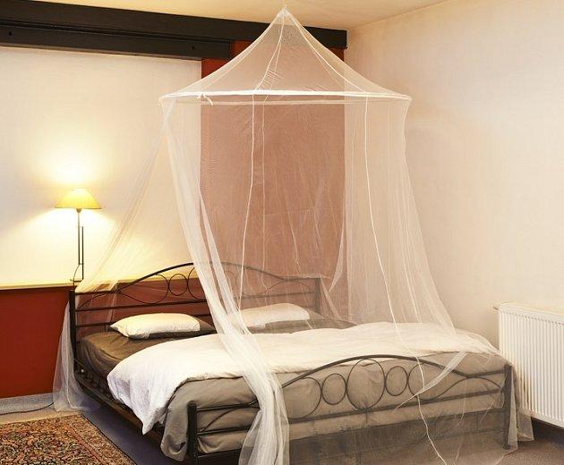Lehká moskytiéra nad postelí může být účinnou ochranou proti komárům