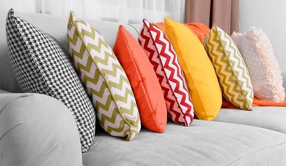 Barevné polštáře vyniknou na jednobarevném podkladě pohovky v šedé barvě.