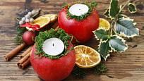 Svícny z jablek přizdobené mechem.