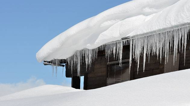 Sníh a rampouchy mohou vážně poškodit střechy.