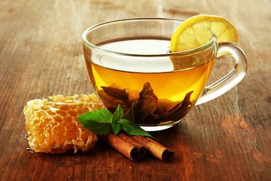 Šálek zeleného čaje s medem a skořicí.