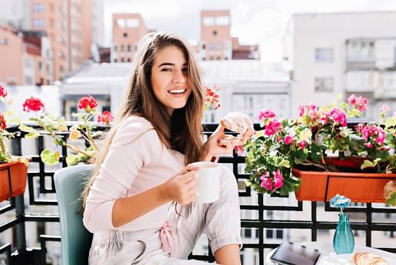 Městský balkon zkrášlený květinami v závěsných truhlících