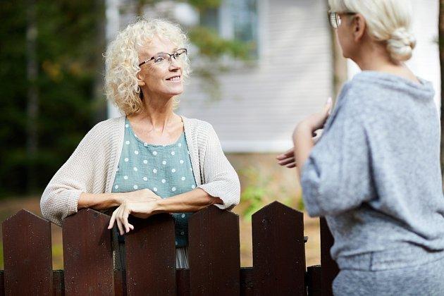 Dvě sousedky povídající si přes plot