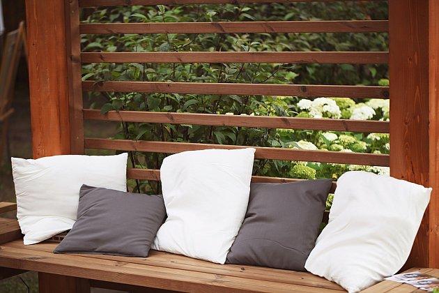 Dřevěnnou lavičku obložte měkkými polštáři.