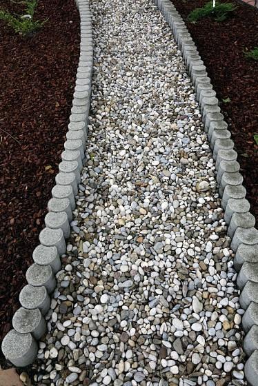 Zahradní pěšinka ze štěrku lemovaná betonovými palisádami.