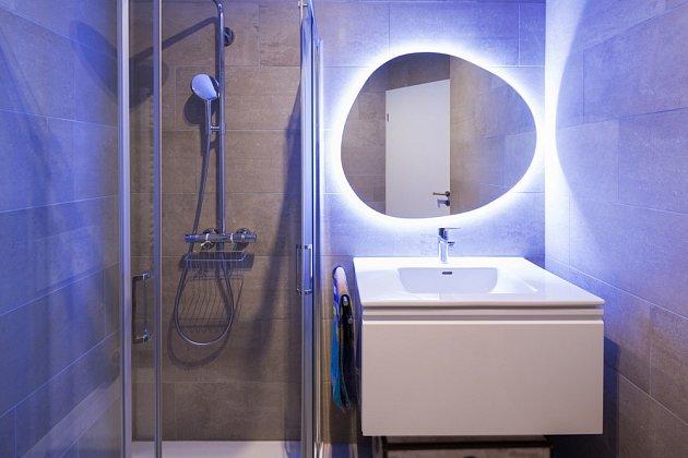 Koupelna s podsvíceným zrcadlem.