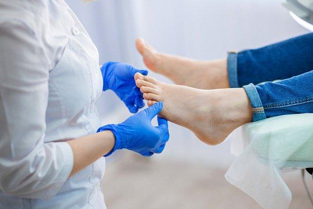 Lékař prohlíží nohy.