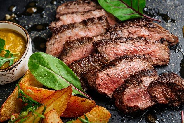 Hovězí hovězí steak z mramoru hovězí středně vzácné s bramborami a omáčkou na kamenné desce