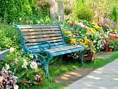 Zahradní lavička v pěkném zákoutí zahrady vybízí k posazení.