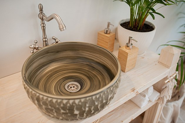 Neobvykle řešené umyvadlo na desku vyrobené z tmavého kamene.