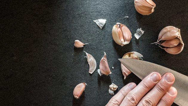 Stroužek si dejte na prkénko a zatlačte na něj naplocho nožem, nebojte se nůž na česnek přimáčknout dlaní.