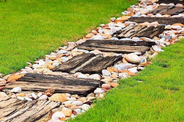 Zahradní cesta ze starého dřeva a kamínků.