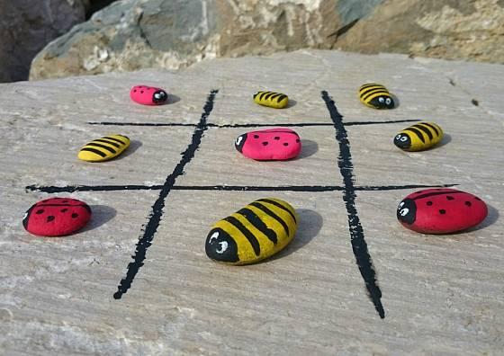 Oblázky malované dvěma odlišnými vzory dobře poslouží jako hrací kameny ke hře Piškvorky.