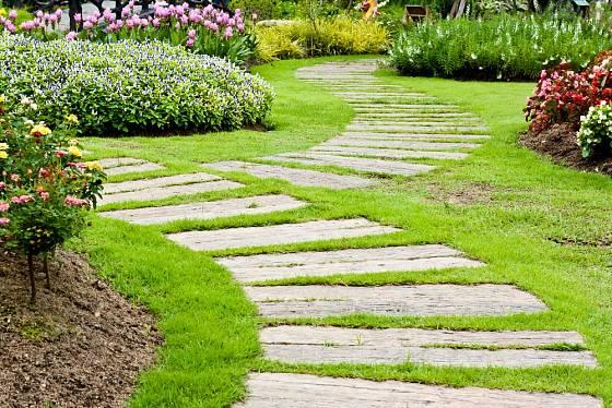 Do trávníku zarostlé dřevěné trámy jsou na zahradních stezkách často vidět.