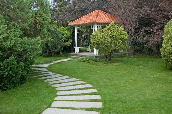 Zvlněná cesta k zahradnímu altánku opticky zahradu zvětšuje.