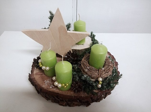 Vánoční dekorace na dřevěném plátu vyzdobená vyřezávanou hvězdou.