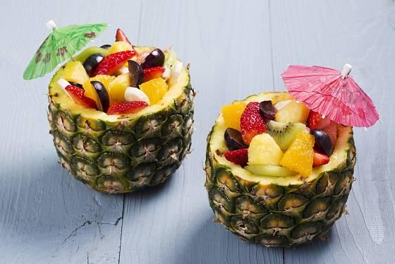 Čerstvý ovocný salát podávaný v miskách vydlabaných z ananasu.
