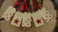 Jmenovky na vánoční dárky přizdobené samolepkami.