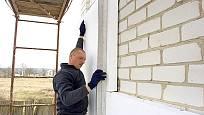 řemeslník zatepluje obvodové zdi polystyrenem