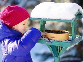 Děti se rády zapojí do doplňování zrní do krmítka.