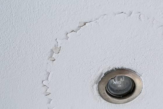 Praskliny na stropě, způsobené zatékající vodou.