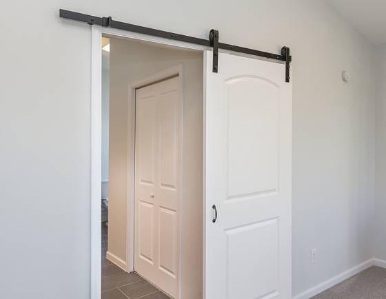 """""""Šoupací"""" dveře se vejdou všude. A jejich uchycení nemusí být zdaleka tak masivní a nápadné, jako toto."""