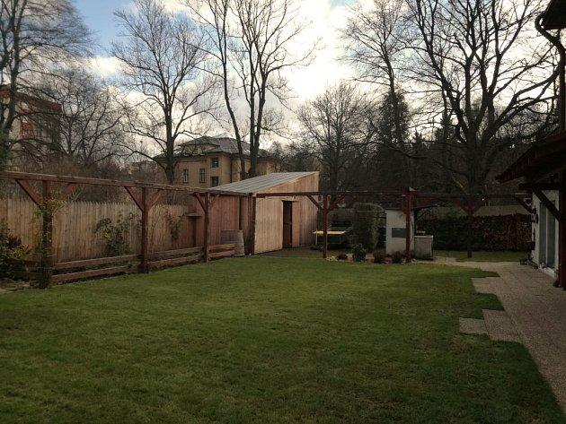 Linie zahradní treláže se protahuje a pozvedá nad plot, stejně jako zdvižená ruka na pozdrav sousedovi za plotem.