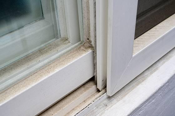 Plastový okenní rám silně znečištěný množstvím prachu.