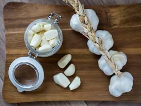 Stroužky česneku oloupeme a vložíme do sklenice.