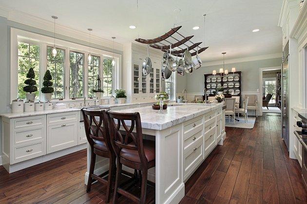 Kuchyně v luxusním domě s bílým granitovým ostrůvkem.