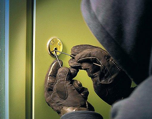 Zloděj paklíčem otvírá dveře