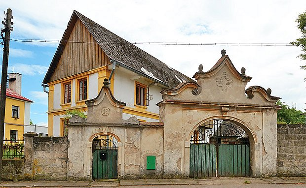 Brána s brankou uzavírá ohrazení usedlosti ve Skalsku. Kdysi měla bohaté zdobení.