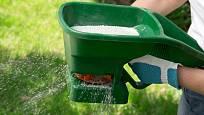 Malé, ručně poháněné rozmetadlo, pro hnojení trávníku.