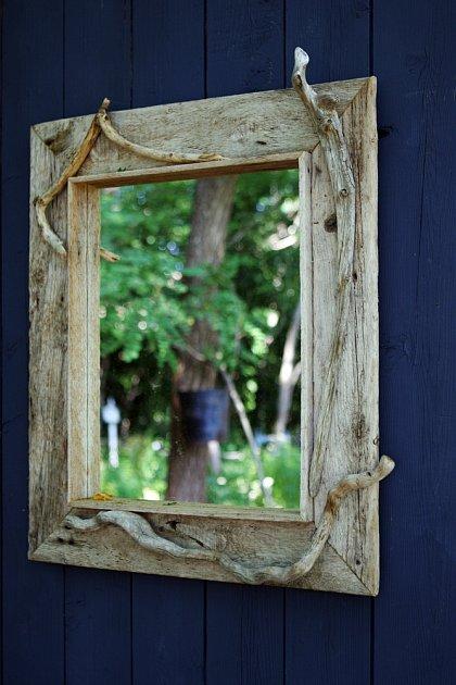 Stylově působící zrcadlo zarámované dřevem s patinou.