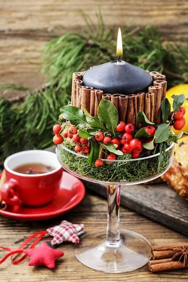 Vánoční svícen přizdobený skořicí, skalníkem a mechem.