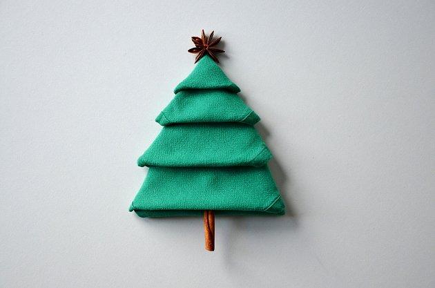 Ubrousek poskládaný do tvaru stromku je půvabnou i užitečnou ozdobou vánočního stolování