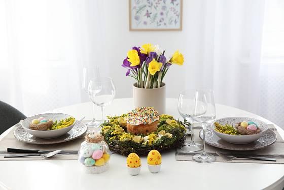 Slavnostní velikonočně vyladěná tabule s vajíčky, jarními květinami a věncem rozzáří celou místnost.