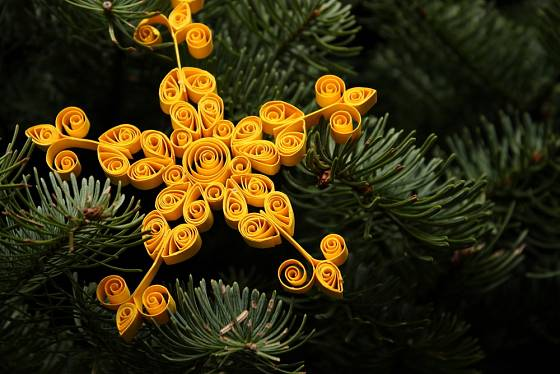Hvězda vyrobená metodou quillingu je slepovaná z částí motaných z barevného papíru.