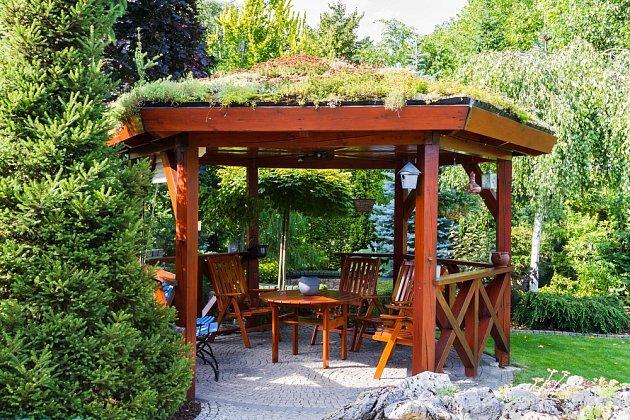 Střechu dřevěného altánu zdobí rostliny a tak dokonale souzní s okolím.