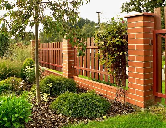 Moderní plotový systém z umělého kamene s dřevěnou výplní.