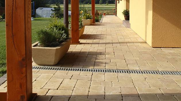 Betonová dlažba se přizpůsobí každému domu. Například ostařený povrch a nepravidelně sražené hrany jako u dlažby BEST – LEGENDA II jsou ideální ke klasickým stavením.