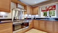 Luxusní moderní vybavená kuchyň se spotřebiči z nerezové oceli, žulovými pracovními plochami a dvěma troubami.