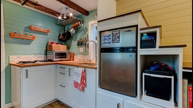 Kuchyň s umyvadlem, lednicí, sporákem, sklopnými židlemi a stolem
