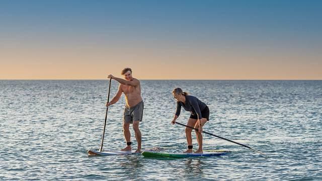 Starší aktivní pár na paddle boardu