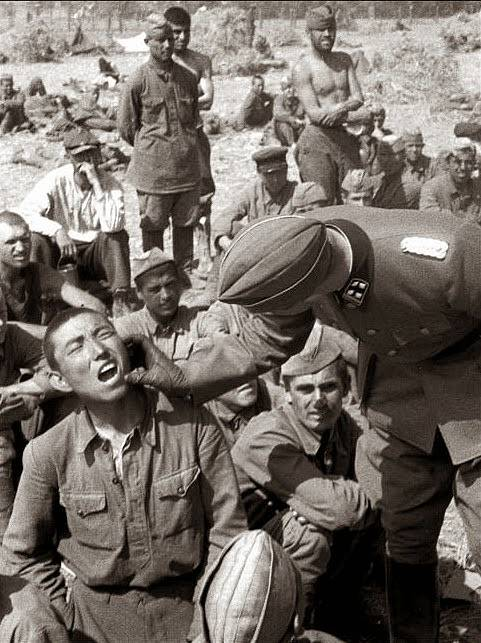 Rok 1941. Dr. Karl Brandt kontroluje chrup sovětského válečného zajatce.