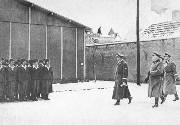 Heinrich Himmler v koncentračním táboru Ravensbrück, leden 1940. Himmler ortopedickými pokusy pověřil dr. Gebhardta.