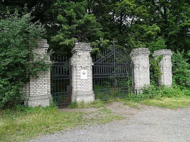 """Za kovovými mřížemi oddělující hřbitov od """"normálního"""" světa se nachází spousta zeleně od vzrostlých stromů po břečťanem pokryté zbytky hrobů."""