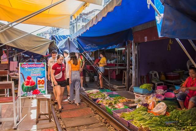 Návštěvníci procházejí podél stánků a jediné, co by je mohlo překvapit, jsou koleje oddělující levou a pravou stranu trhu