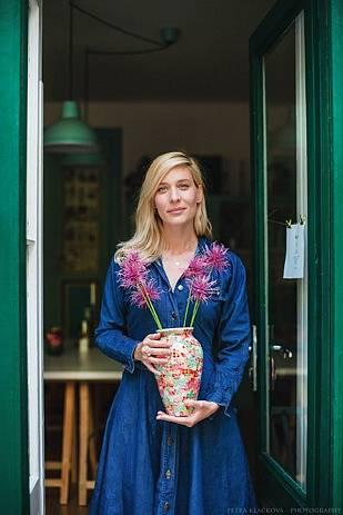 Tady drží v rukou velkou vázu zdobenou decoupagí se secesními motivy květů.
