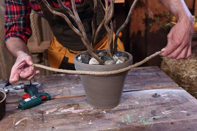 Kolem květináče omotejte přírodní provázek a připevněte ho pomocí lepicí tavné pistole.